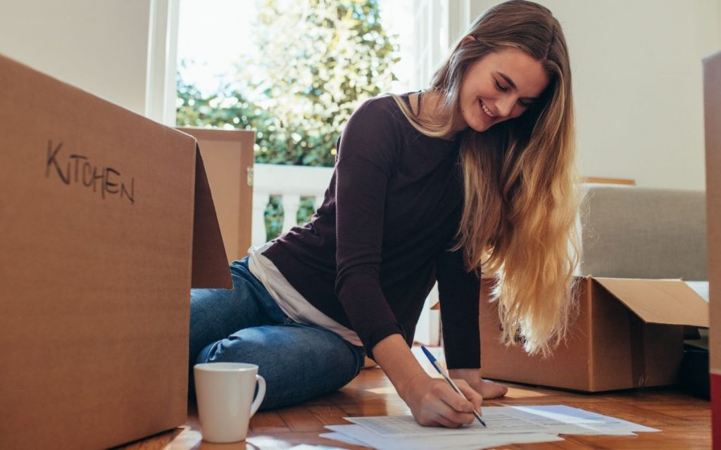 woman packing boxes and making a list